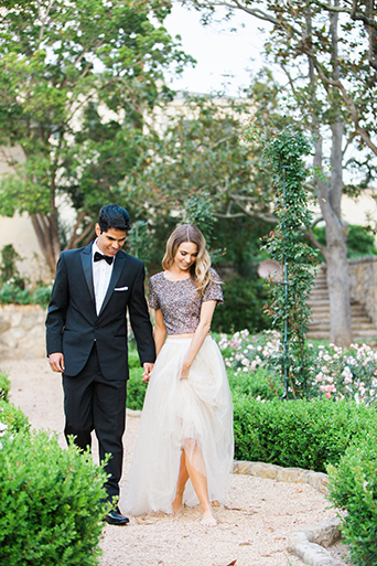 Santa barbara engagement shoot bride silver sequined crop top with long white tulle skirt with groom black tuxedo with white dress shirt and black bow tie with white pocket square walking and holding hands