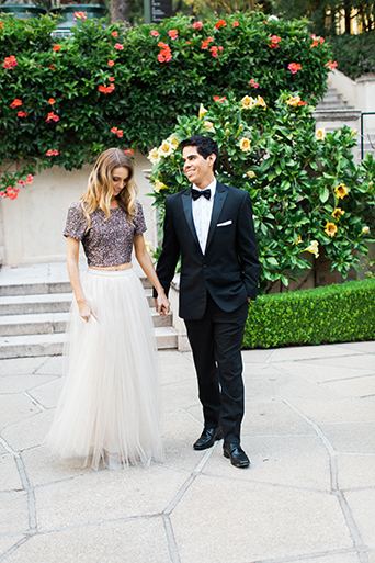 Santa barbara engagement shoot bride silver sequined crop top with long white tulle skirt with groom black tuxedo with white dress shirt and black bow tie with white pocket square holding hands