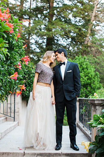 Santa barbara engagement shoot bride silver sequined crop top with long white tulle skirt with groom black tuxedo with white dress shirt and black bow tie with white pocket square kissing with flowers in background