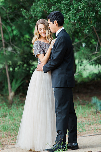 Santa barbara engagement shoot bride silver sequined crop top with long white tulle skirt with groom black tuxedo with white dress shirt and black bow tie with white pocket square