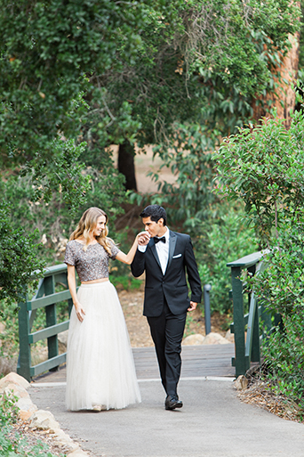 Santa barbara engagement shoot bride silver sequined crop top with long white tulle skirt with groom black tuxedo with white dress shirt and black bow tie with white pocket square kissing brides hand