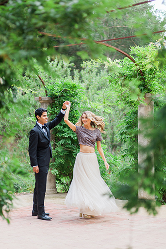 Santa barbara engagement shoot bride silver sequined crop top with long white tulle skirt with groom black tuxedo with white dress shirt and black bow tie with white pocket square spinning and dancing