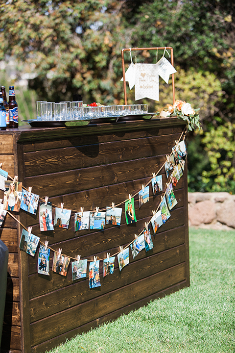 Chilean inspired outdoor wedding at quail ranch rustic wood bar set up with hanging picture collage decor on outside with glasses and assortment of beverages
