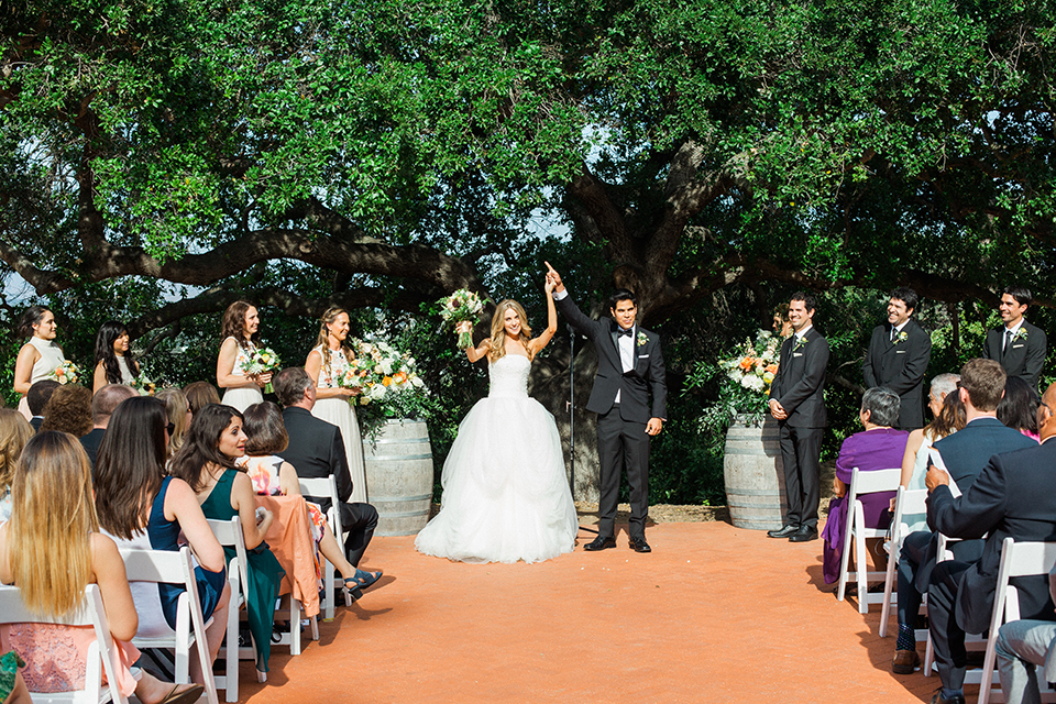 Chilean inspired outdoor wedding at quail ranch bride strapless gown with straight neckline and lace detail on bodice and groom black notch lapel tuxedo with white dress shirt and black bow tie with white pocket square and white floral boutonniere cheering after ceremony