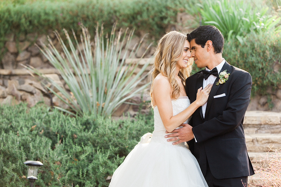 Chilean inspired outdoor wedding at quail ranch bride strapless gown with straight neckline and lace detail on bodice and groom black notch lapel tuxedo with white dress shirt and black bow tie with white pocket square and white floral boutonniere hugging