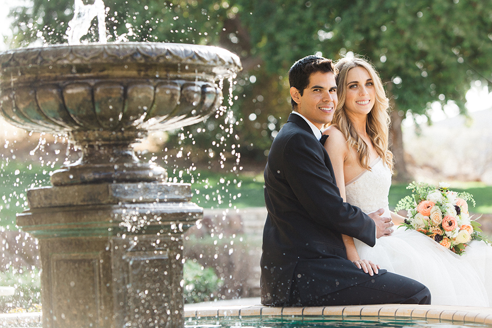 Chilean inspired outdoor wedding at quail ranch bride strapless gown with straight neckline and lace detail on bodice and groom black notch lapel tuxedo with white dress shirt and black bow tie with white pocket square and white floral boutonniere sitting by fountain bride holding white floral bridal bouquet