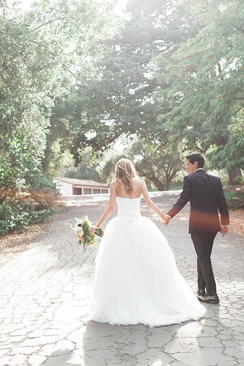 Chilean inspired outdoor wedding at quail ranch bride strapless gown with straight neckline and lace detail on bodice and groom black notch lapel tuxedo with white dress shirt and black bow tie with white pocket square and white floral boutonniere holding hands and bride holding white floral bridal bouquet