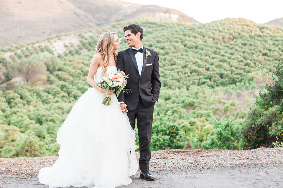 Chilean inspired outdoor wedding at quail ranch bride strapless gown with straight neckline and lace detail on bodice and groom black notch lapel tuxedo with white dress shirt and black bow tie with white pocket square and white floral boutonniere bride holding white floral bridal bouquet