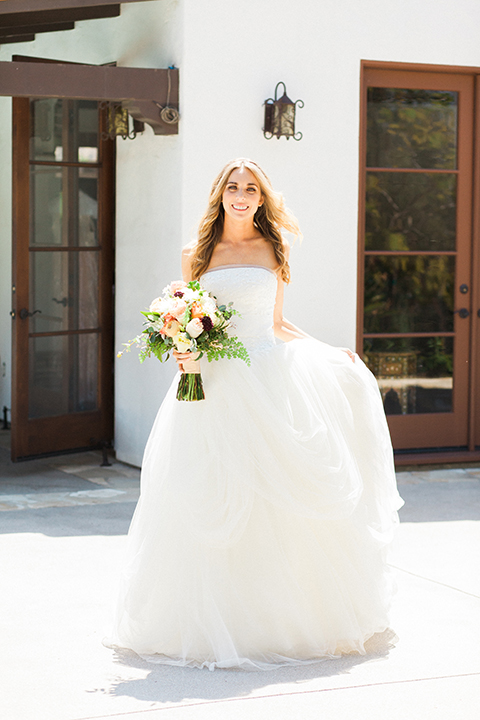 Chilean inspired outdoor wedding at quail ranch bride strapless gown with straight neckline and lace detail on bodice with crystal headband holding white floral bridal bouquet and dress wedding photo idea for bride