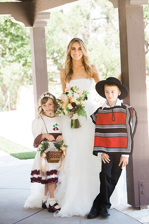 Chilean inspired outdoor wedding at quail ranch bride strapless gown with straight neckline and lace detail on bodice with crystal headband with ring bearer and flower girl wearing traditional chilean clothing