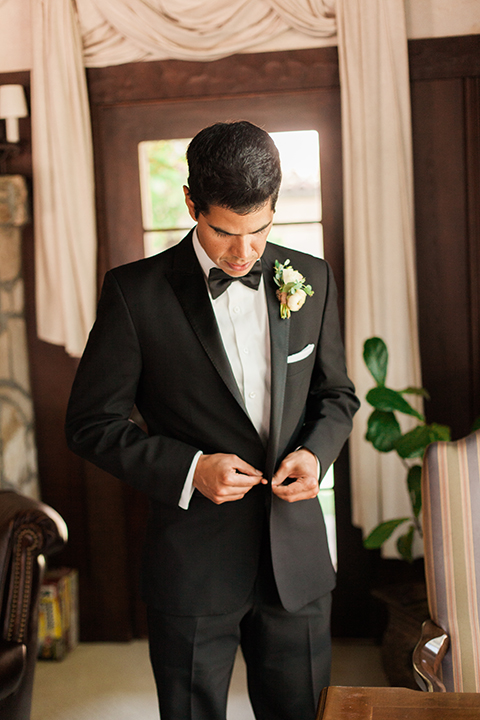 Chilean inspired outdoor wedding at quail ranch groom black notch lapel tuxedo with white dress shirt and black bow tie with white pocket square and white floral boutonniere and cufflinks with black watch