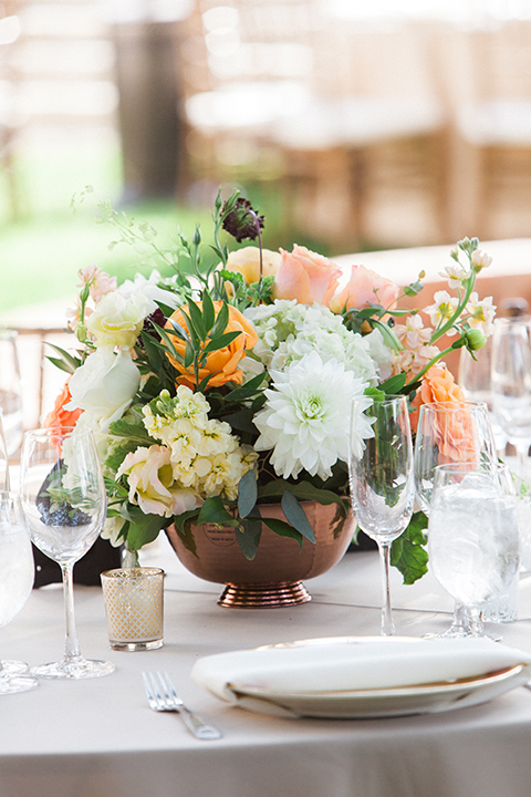 Chilean inspired outdoor wedding at quail ranch reception table set up with champagne table linen and gold chairs with white place settings and white and light orange and peach flower centerpiece decor in copper vase on grass