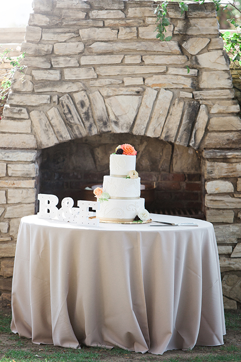 Chilean inspired outdoor wedding at quail ranch reception table set up with champagne table linen and gold chairs with white place settings and white and light orange and peach flower centerpiece decor in copper vase on grass with bride and grooms initials and white three tier wedding cake