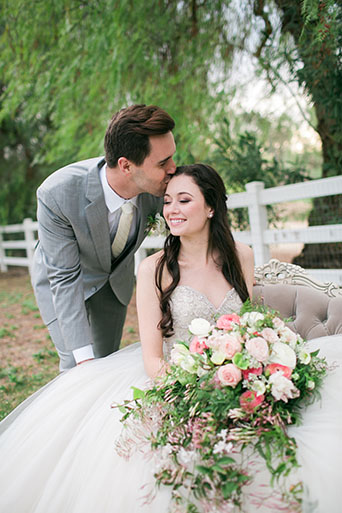 Two sisters farms fairytale wedding bride strapless ball gown with a sweetheart neckline and beaded bodice with white and pink floral bridal bouquet and groom heather grey suit with matching vest and white dress shirt with long white tie and white floral boutonniere