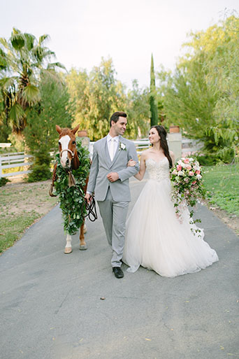Two sisters farms fairytale wedding bride strapless ball gown with a sweetheart neckline and beaded bodice with white and pink floral bridal bouquet and groom heather grey suit with matching vest and white dress shirt with long white tie and white floral boutonniere walking next to horse
