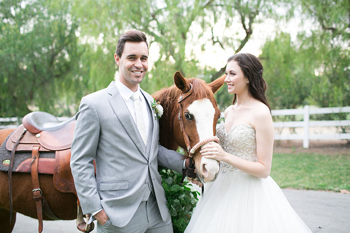 Two sisters farms fairytale wedding bride strapless ball gown with a sweetheart neckline and beaded bodice with white and pink floral bridal bouquet and groom heather grey suit with matching vest and white dress shirt with long white tie and white floral boutonniere with horse