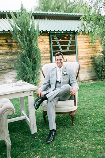 Two sisters farms fairytale wedding groom heather grey suit with matching vest and white dress shirt with long white tie and white floral boutonniere sitting at table with white vintage chairs