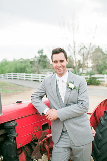 Two sisters farms fairytale wedding groom heather grey suit with matching vest and white dress shirt with long white tie and white floral boutonniere standing by red tractor