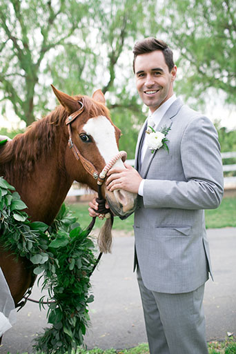 Two sisters farms fairytale wedding groom heather grey suit with matching vest and white dress shirt with long white tie and white floral boutonniere standing by horse