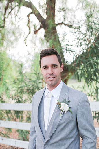 Two sisters farms fairytale wedding groom heather grey suit with matching vest and white dress shirt with long white tie and white floral boutonniere