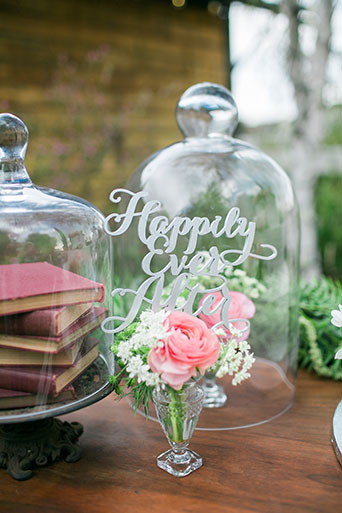 Two sisters farms fairytale wedding pink rose flower in crystal glass case that says happily ever after and vintage books decor on brown wood table wedding photo idea