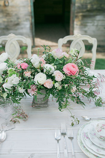 Two sisters farms fairytale wedding white table with white vintage chairs and grey vintage bench with white and pink flower centerpiece decor with white and pink flower place settings and pink crystal glasses