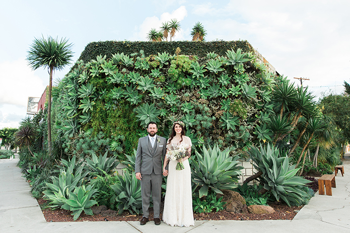 Los angeles wedding at smogshoppe bride a line lace gown with short sleeves and green and white flower crown with groom grey suit with matching vest and white dress shirt with long tie standing in front of green floral wall