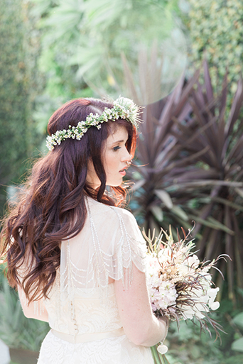 Los angeles wedding at smogshoppe bride a line lace gown with short sleeves and ribbon belt with green and white flower crown holding white floral bridal bouquet