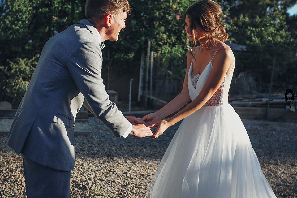 Big red barn styled wedding shoot bride tulle ball gown with lace detail on top and thin straps with groom heather grey suit with matching vest and white dress shirt with light green bow tie and matching pocket square holding hands after first look