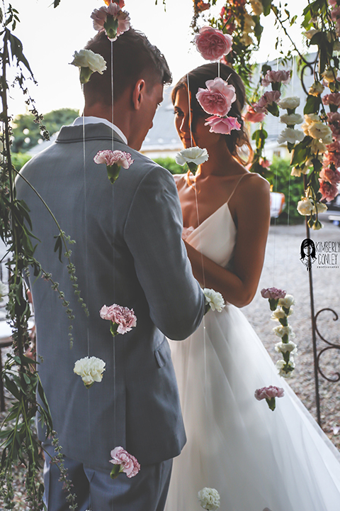 Big red barn styled wedding shoot bride tulle ball gown with lace detail on top and thin straps with groom heather grey suit with matching vest and white dress shirt with light green bow tie and matching pocket square holding hands during ceremony with pink hanging flower decor