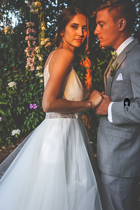 Big red barn styled wedding shoot bride tulle ball gown with lace detail on top and thin straps with groom heather grey suit with matching vest and white dress shirt with light green bow tie and matching pocket square holding hands with pink flower hanging decor