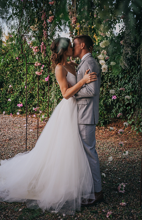 Big red barn styled wedding shoot bride tulle ball gown with lace detail on top and thin straps with groom heather grey suit with matching vest and white dress shirt with light green bow tie and matching pocket square