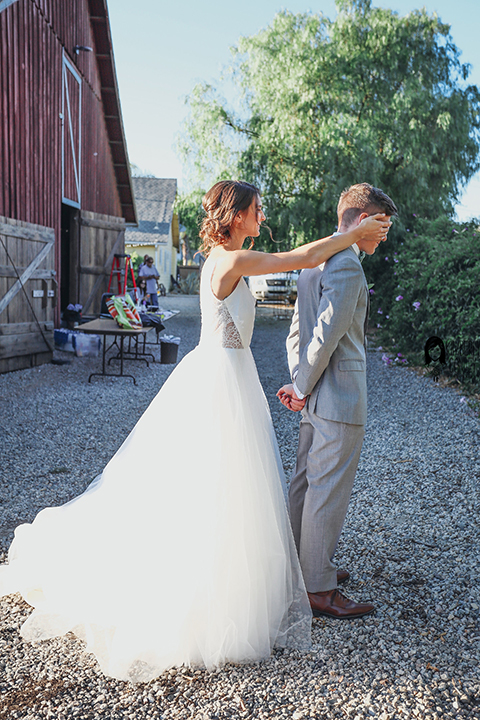 Big red barn styled wedding shoot bride tulle ball gown with lace detail on top and thin straps with groom heather grey suit with matching vest and white dress shirt with light green bow tie and matching pocket square bride covering grooms eyes for first look