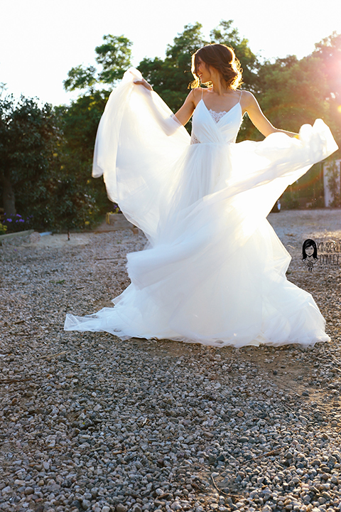 Big red barn styled wedding shoot bride tulle ball gown with lace detail on top and thin straps and hair updo playing with dress