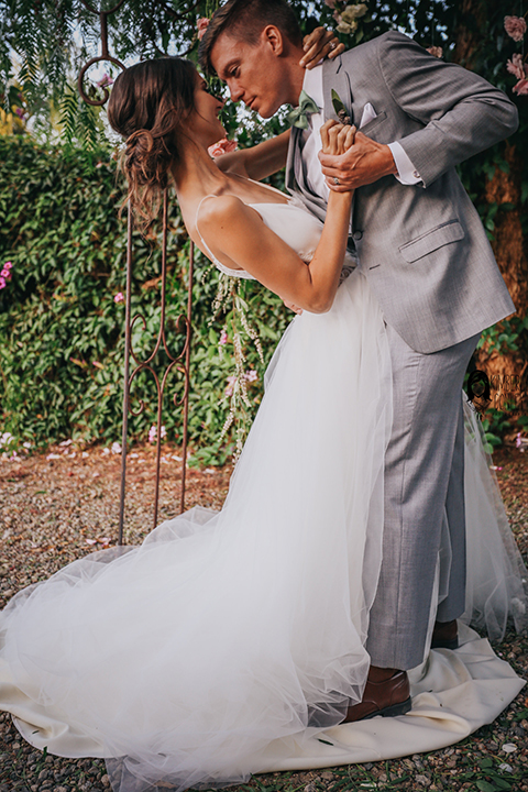 Big red barn styled wedding shoot bride tulle ball gown with lace detail on top and thin straps with groom heather grey suit with matching vest and white dress shirt with light green bow tie and matching pocket square groom dipping bride