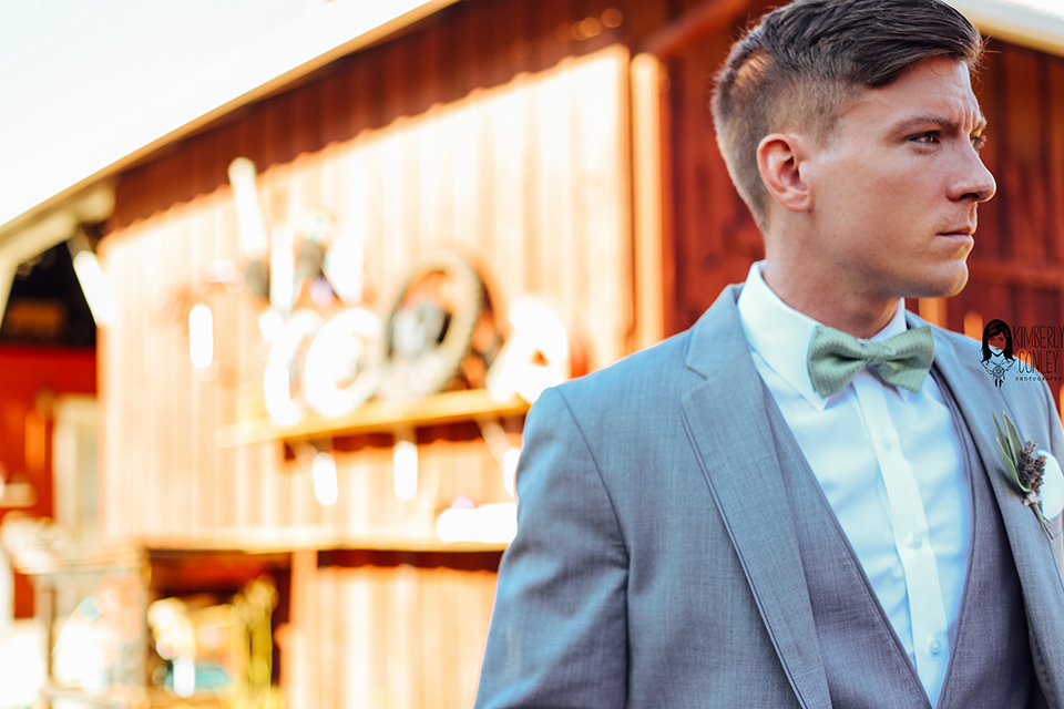 Big red barn styled wedding shoot groom heather grey suit with matching vest and white dress shirt with light green bow tie and matching pocket square