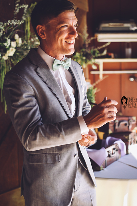 Big red barn styled wedding shoot groom heather grey suit with matching vest and white dress shirt with light green bow tie and matching pocket square putting on jacket and fixing sleeve