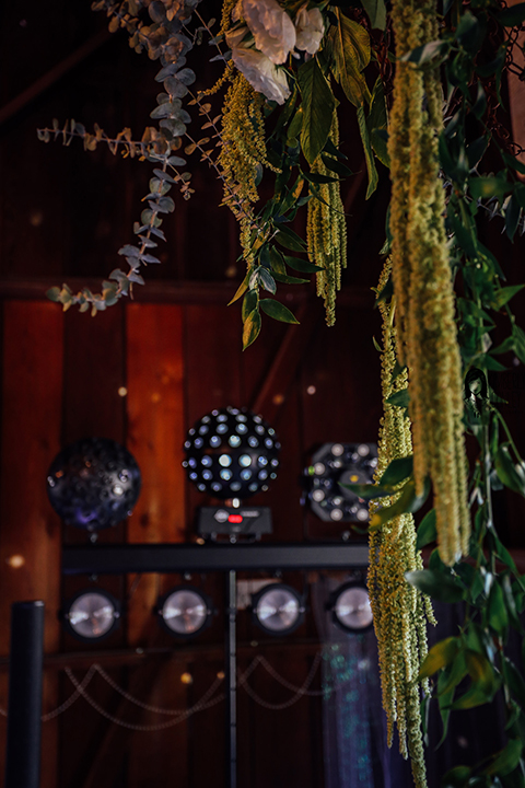 Big red barn styled wedding shoot hanging greenery garland floral decor inside reception with disco ball decor and sound system