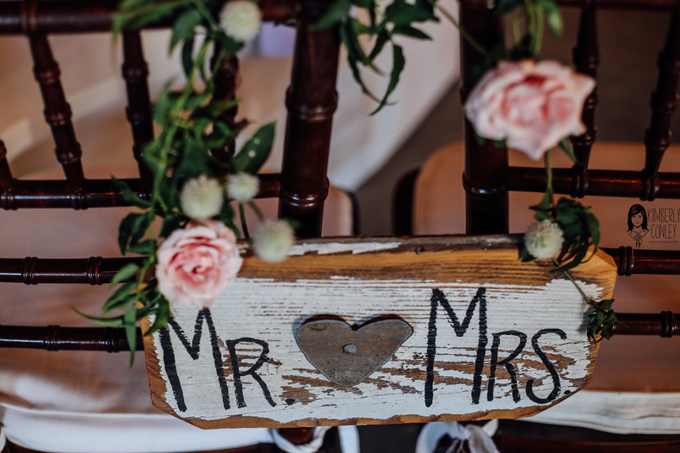 Big red barn styled wedding shoot brown wood sign with black and white paint writing mr. and mrs. hanging on chairs with pink and white flower decor