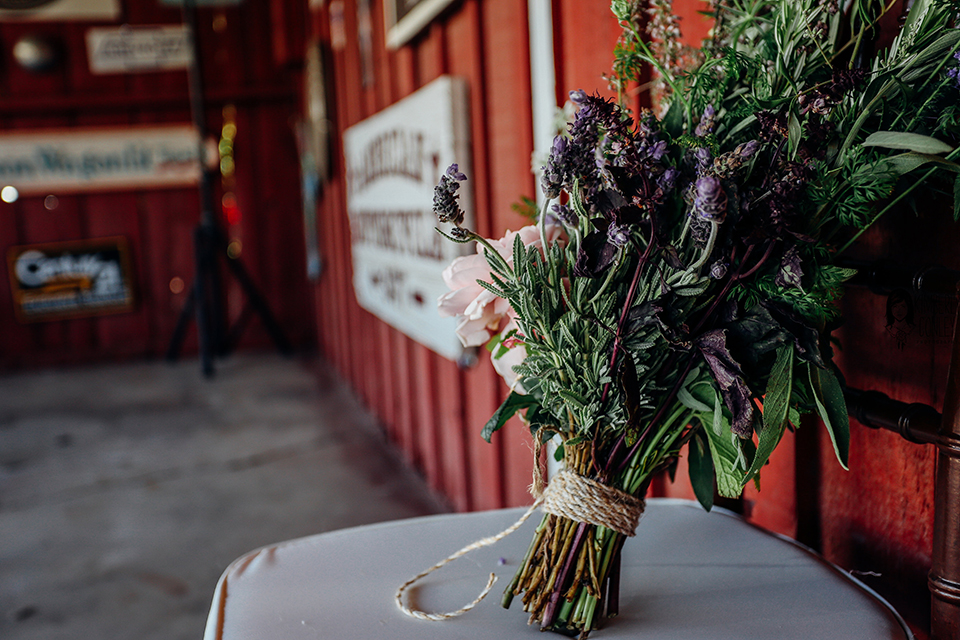 Big red barn styled wedding shoot lavender floral bridal bouquet with greenery decor and white ribbon decor sitting on white table