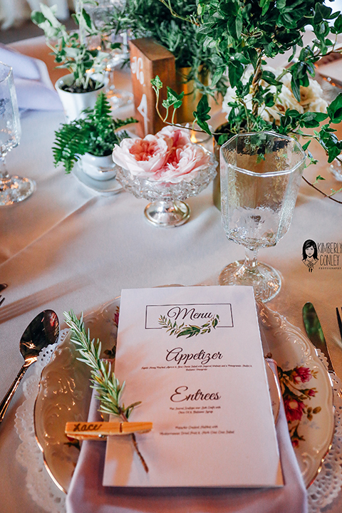 Big red barn styled wedding shoot white table linen with white menu and white place setting with greenery floral centerpiece decor with crystal glasses