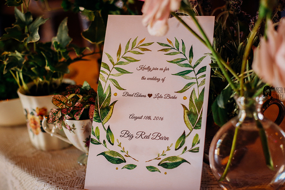 Big red barn styled wedding shoot white table linen with white wedding invitation and greenery floral decor wedding photo idea