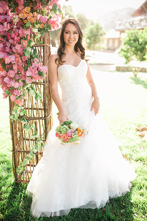 Giracci farms outdoor wedding bride strapless mermaid style gown with a ruffled skirt and lace detail and holding bright pink and orange floral bridal bouquet