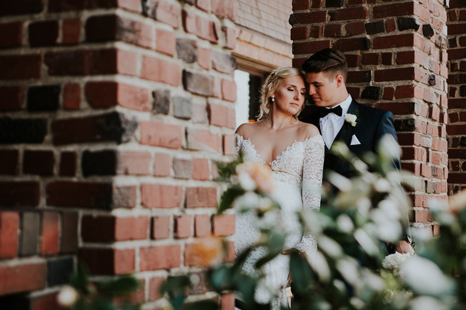 Modern outdoor wedding at long beach museum of art bride mermaid style lace gown with long sleeves and plunging neckline with illusion buttons on back and groom navy blue tuxedo with matching vest and white dress shirt with black bow tie and white pocket square with white floral boutonniere hugging by brick wall
