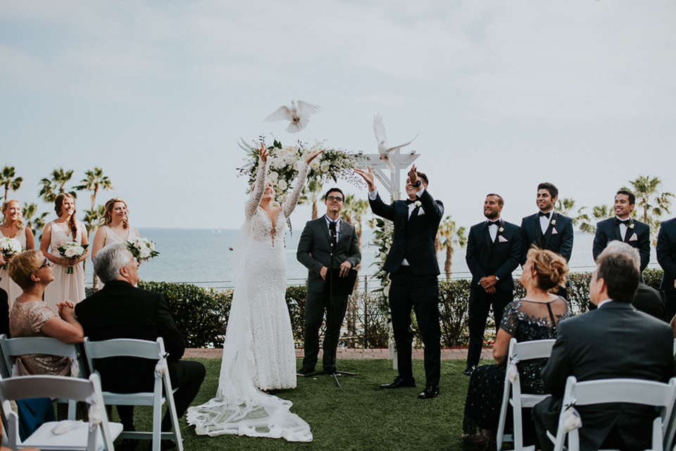 Modern outdoor wedding at long beach museum of art bride mermaid style lace gown with long sleeves and plunging neckline with illusion buttons on back and groom navy blue tuxedo with matching vest and white dress shirt with black bow tie and white pocket square with white floral boutonniere releasing doves for ceremony