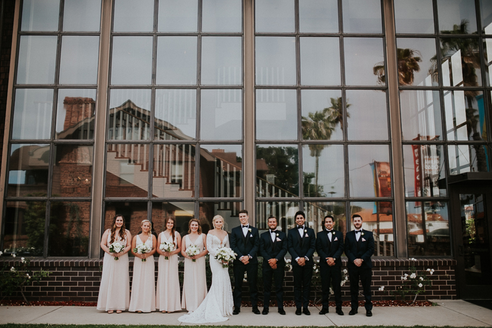 Modern outdoor wedding at long beach museum of art bride mermaid style lace gown with long sleeves and plunging neckline with illusion buttons on back and groom navy blue tuxedo with matching vest and white dress shirt with black bow tie and white pocket square with white floral boutonniere with bridesmaids long champagne dresses with white floral bridal bouquets and groomsmen navy tuxedos with black bow ties