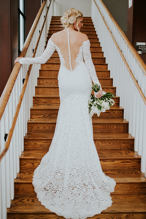 Modern outdoor wedding at long beach museum of art bride mermaid style lace gown with long sleeves and plunging neckline with illusion buttons on back holding white floral bridal bouquet