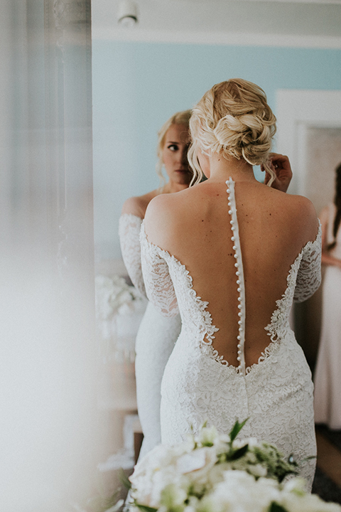 Modern outdoor wedding at long beach museum of art bride mermaid style lace gown with long sleeves and plunging neckline with illusion buttons on back holding white floral bridal bouquet putting on earrings in mirror