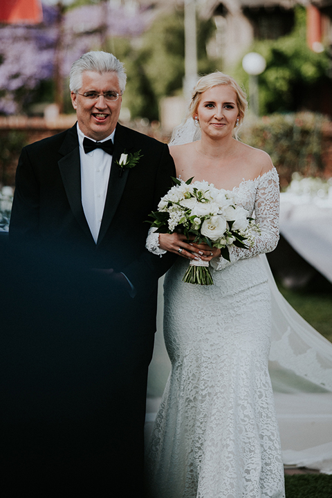 Modern outdoor wedding at long beach museum of art bride mermaid style lace gown with long sleeves and plunging neckline with illusion buttons on back holding white floral bridal bouquet walking down the aisle with dad black tuxedo with black bow tie