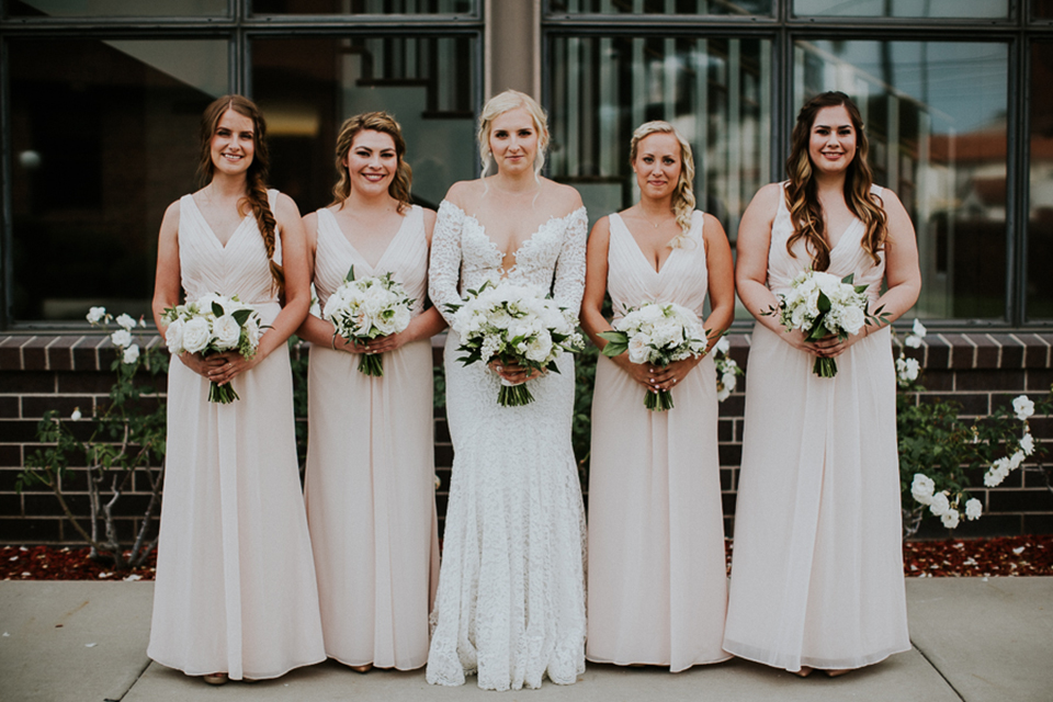 Modern outdoor wedding at long beach museum of art bride mermaid style lace gown with long sleeves and plunging neckline with illusion buttons on back holding white floral bridal bouquet with bridesmaids long champagne dresses with white floral bridal bouquets